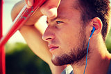 young man with earphones and horizontal bar