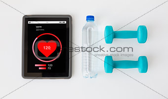close up of tablet pc, dumbbells and water bottle