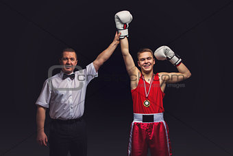 Boxing referee gives medal to young boxer