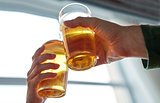 close up of hands clinking beer glasses at pub