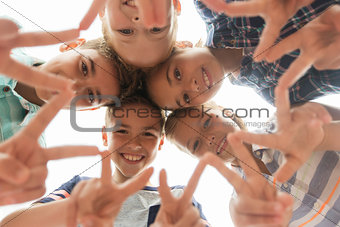 group of happy children showing v sign in circle