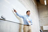 teacher pointing marker to white board at lecture