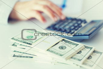 close up of hand counting money with calculator