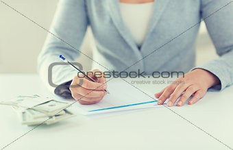 close up of hands with money filling tax form