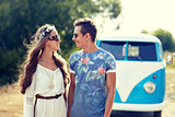 smiling young hippie couple over minivan car