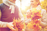 smiling couple with maple leaves in autumn park