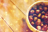 close up of chestnuts in basket on wooden table
