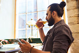 man with smartphone drinking beer at bar or pub