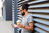 man with coffee texting on smartphone in city