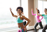 group of smiling woman dancing in gym or studio