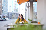 happy woman calling on smartphone at city cafe