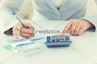 close up of hands counting money with calculator