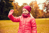 happy little girl waving hand in autumn park