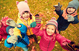 happy children waving hands in autumn park