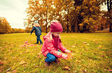 children collecting leaves in autumn park