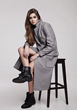 Beautiful young girl wearing long grey jacket