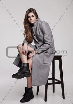 Beautiful young girl wearing long grey jacket