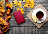 Cup of tea with lemon with scarf and autumn leaves