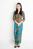 Southeast Asian girl in batik dress smiling