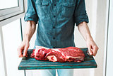 Man`s hands holding  rustic tray with raw beef meet