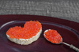 Sandwich with red caviar in the form of heart on a wooden tray. Analog products.