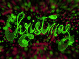 Christmas word lettering written with green fire flame or smoke on blurred bokeh background