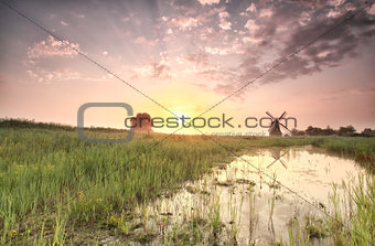 beautiful summer sunrise over windmill by river