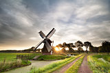 morning sunshine behind old Dutch windmill in summer