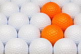 White and orange golf balls in the box
