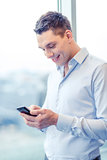 smiling businessman with smartphone in office