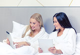 girlfriends with tablet pc computers in bed