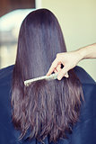 hand with comb combing woman hair at salon