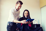 happy woman and stylist with tablet pc at salon