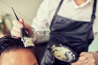 close up of stylist coloring hair at salon