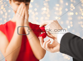close up of woman and man with engagement ring