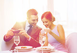 smiling couple with appetizers and smartphones