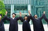 happy students or bachelors celebrating graduation