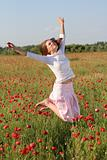 Girl jumps over poppy field
