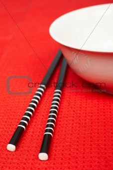 Pair of chopsticks and white bowl