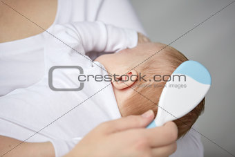 close up of mother brushing newborn baby hair