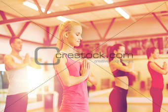 group of smiling people meditating in the gym