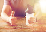 man with protein shake bottle showing thumbs up