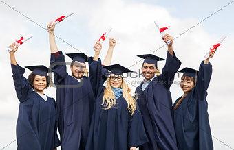 happy students in mortar boards waving diplomas