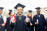 happy students with diplomas showing thumbs up