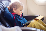 Little boy using tablet on board of aircraft
