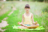 Young girl relaxing while sitting in lotus position outdoors