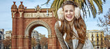 happy elegant woman in earmuffs in Barcelona, Spain standing