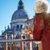Closeup on Venetian mask in hand of woman on embankment