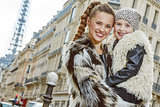 smiling mother and child nearby Eiffel tower in Paris, France
