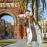 woman in Barcelona, Spain taking selfie with smartphone